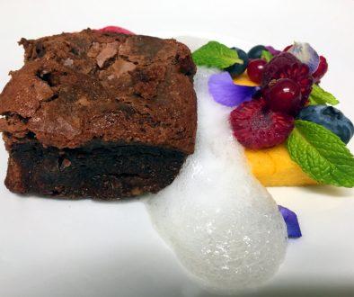Emplatado del brownie con esponja de maracuya y sorbete de frambuesa y aire de cava